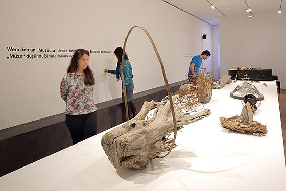Visitors looking at the exhibits, that are made out of wood and roots and presented on a long white table.