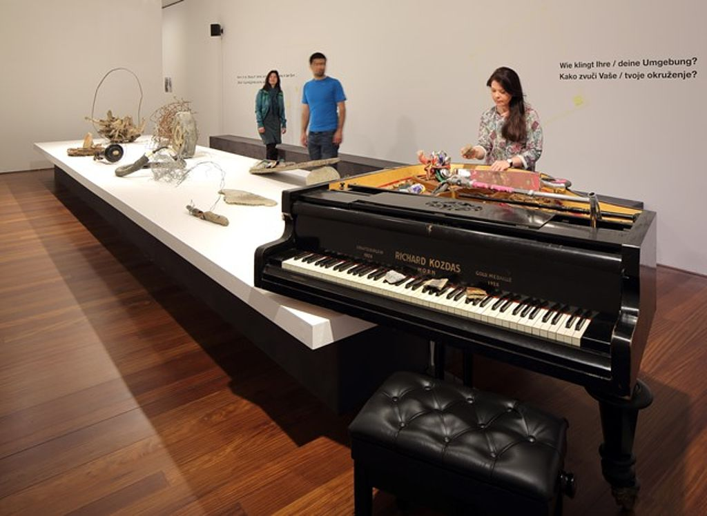 In the foreground a black piano is displayed, with its cover opened and visitors standing behind.