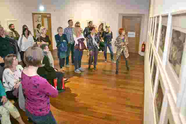 A group of people participate in a guided tour through an exhibition at the Rupertinum