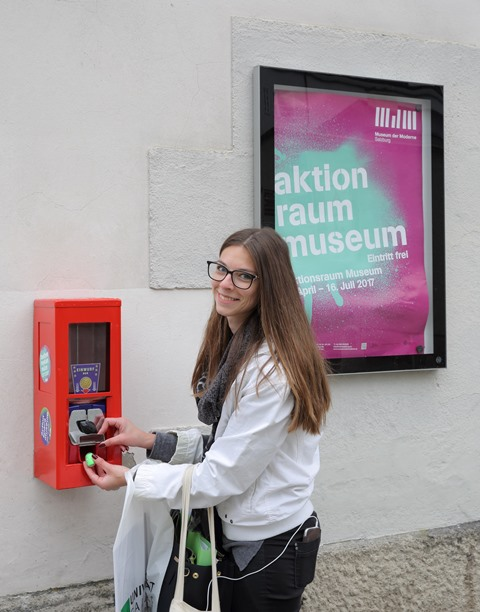 A young woman takes a plastic ball out of a chewing gum machinge, to her right is the poster for the exhibition that shows the title of the exhibition.